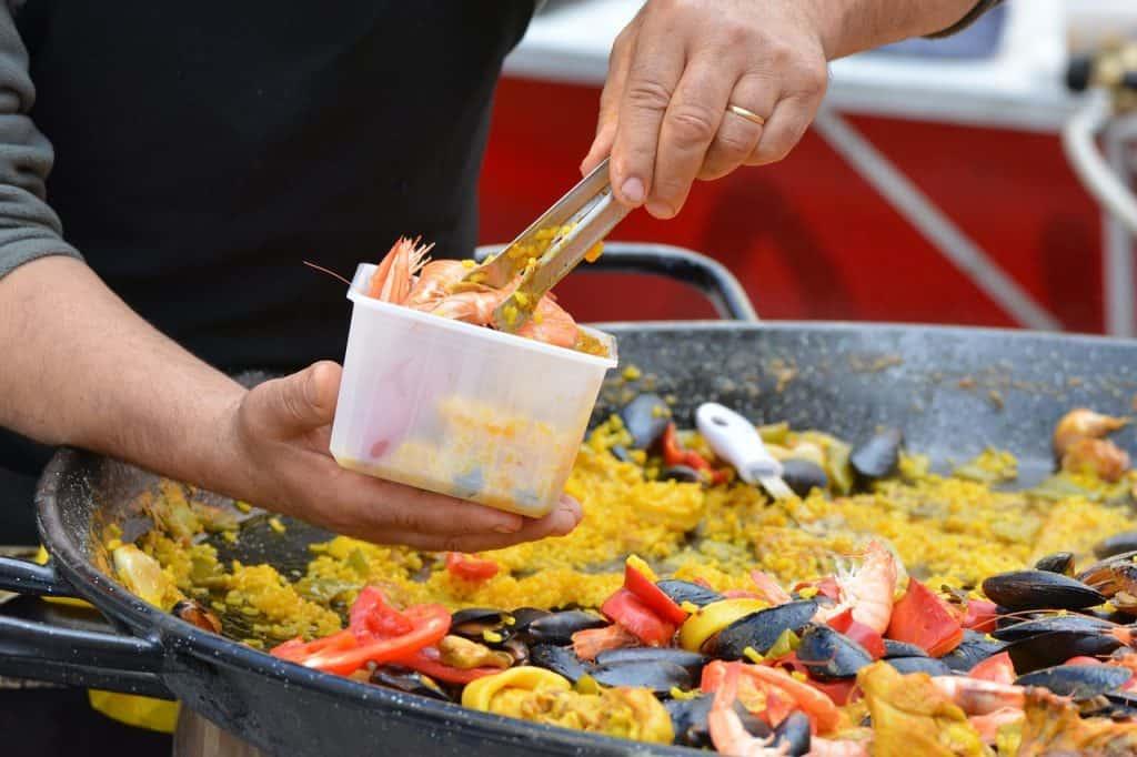 Imagem de uma pessoa acrescentando frutos do mar a uma paella.