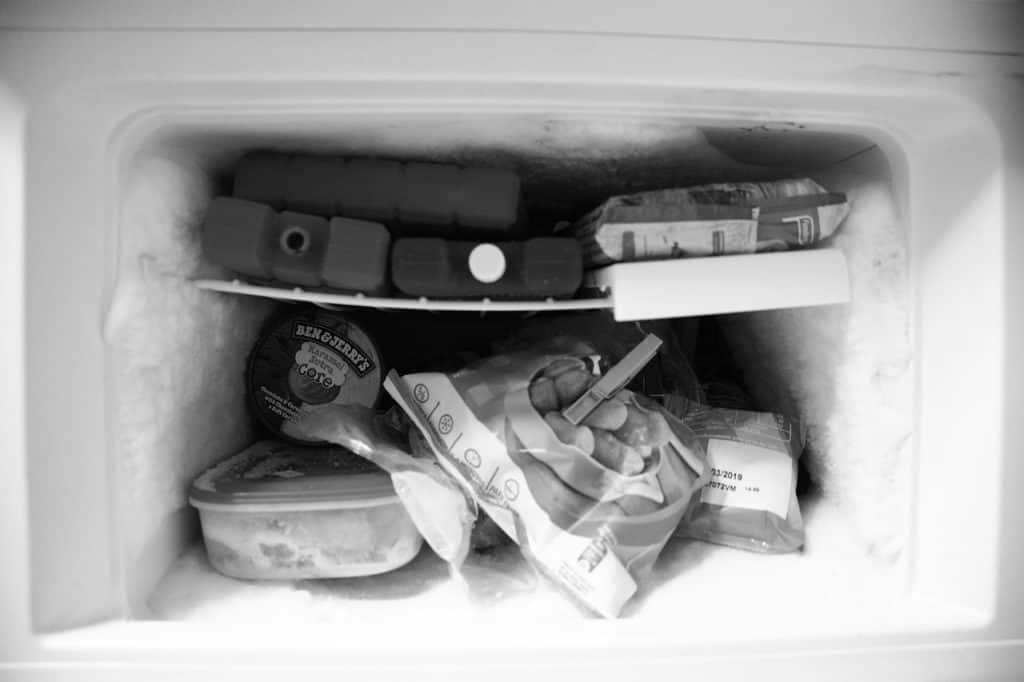 Imagem mostra um freezer com diversos alimentos dentro.