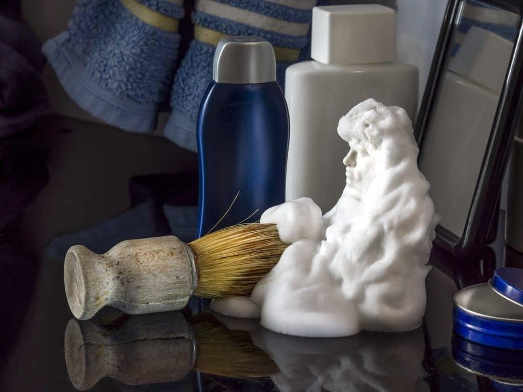 Imagem mostra uma prateleira de barbearia com alguns frascos e um homem feito de creme de barbear.
