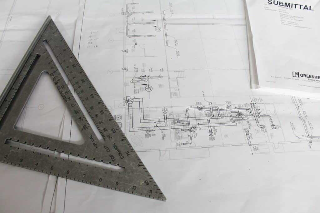 Imagem mostra um esquadro rígido sob um papel, ao lado de um elaborado projeto desenhado.