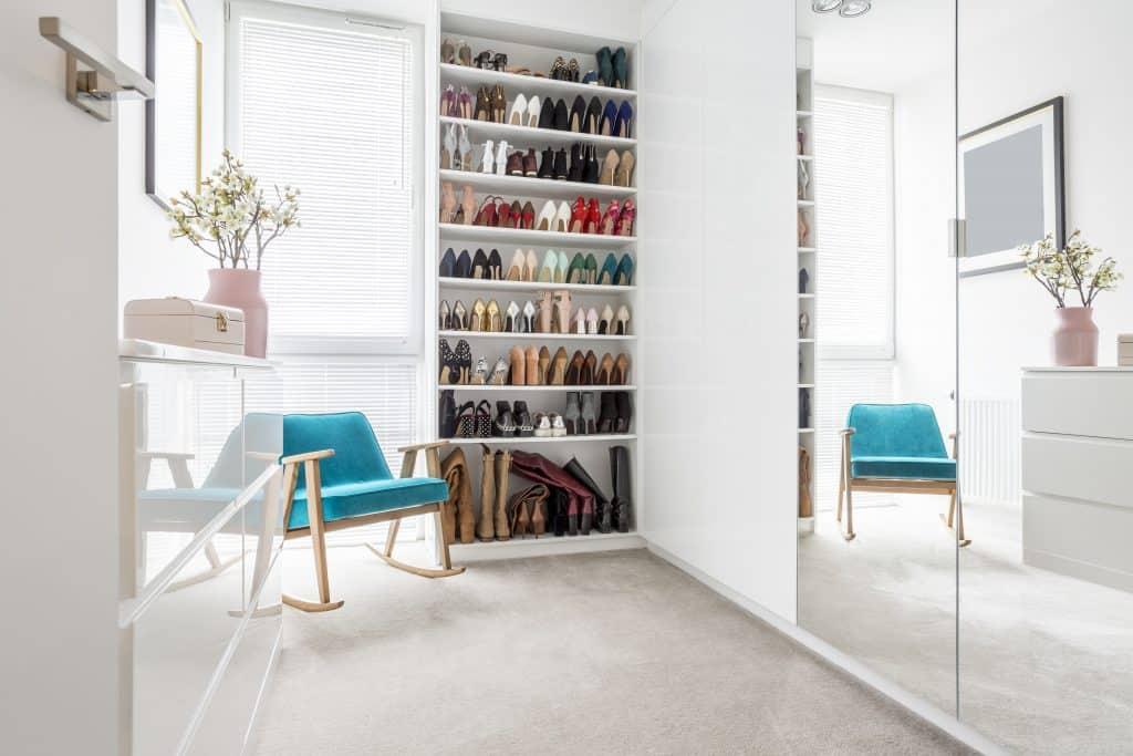 Closet com sapateira, espelho, armários e poltrona.