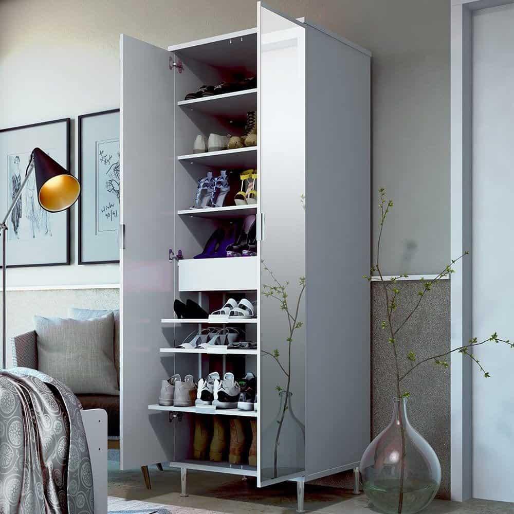 Sapateira com espelho com portas abertas e sapatos dentro em um lindo quarto decorado.