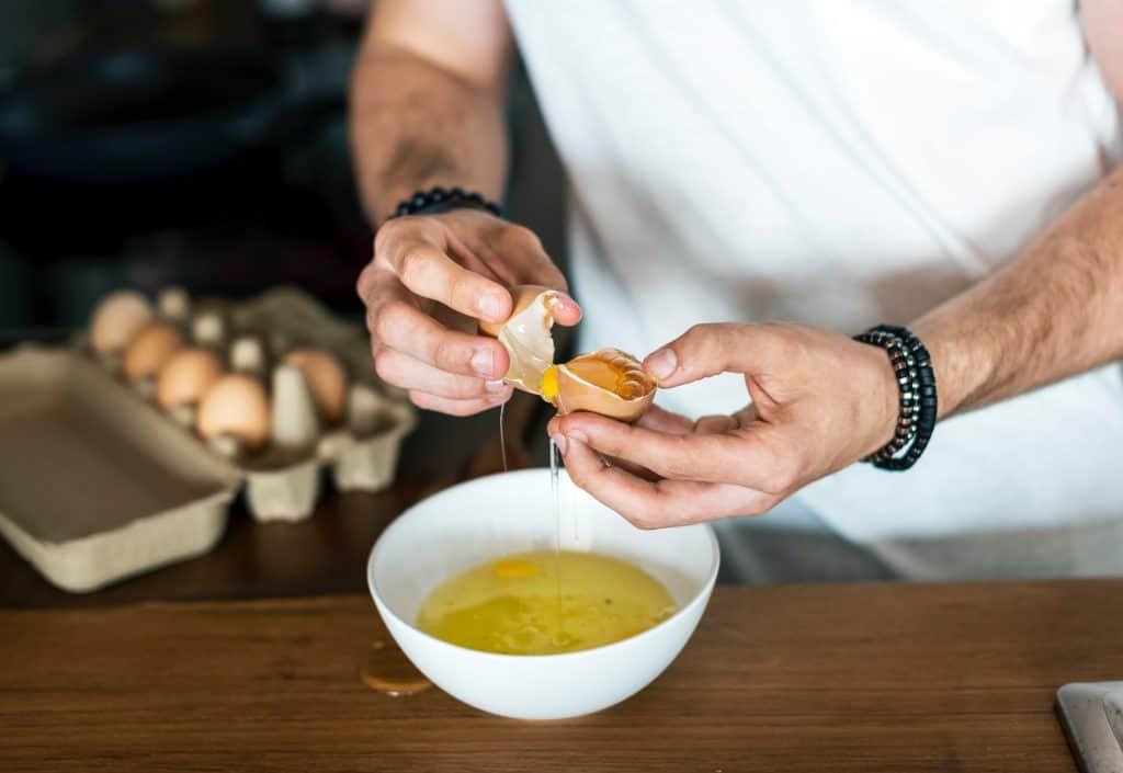 Imagem de um homem quebrando ovos em uma tigela.