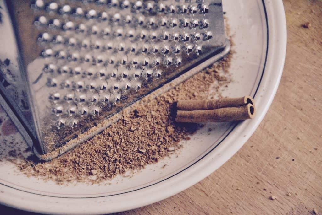 Ralador com canela recém-ralada em um prato e um pedaço de pau de canela ao lado.