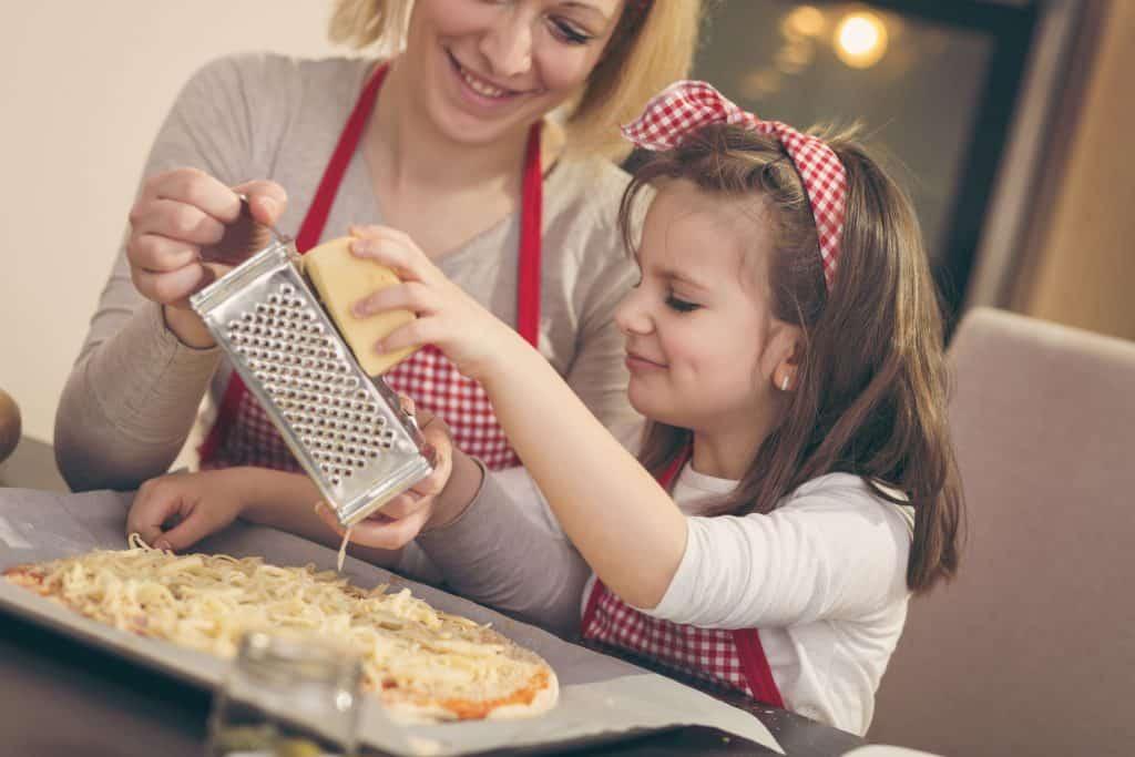 Mulher na bancada da cozinha ralando uma peça de queijo com filha.