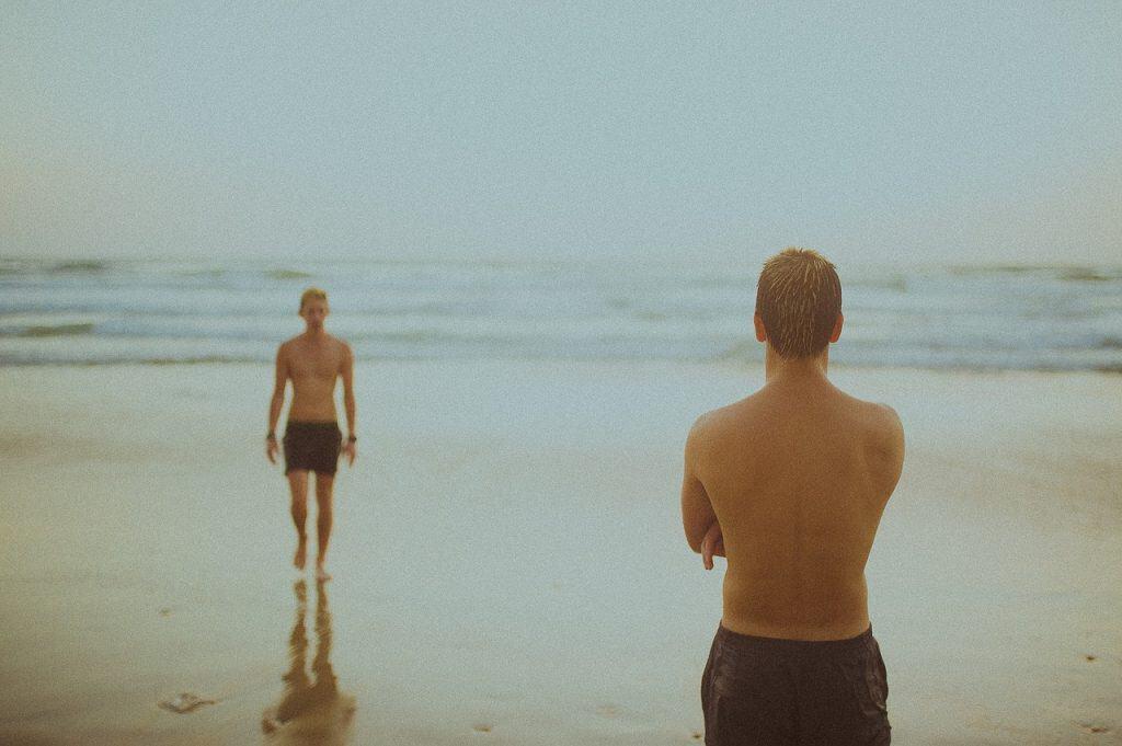 Imagem mostra dois rapazes na praia, com o mar ao fundo. Um está saindo da água, enquanto o outro, também molhado, observa de braços cruzados.
