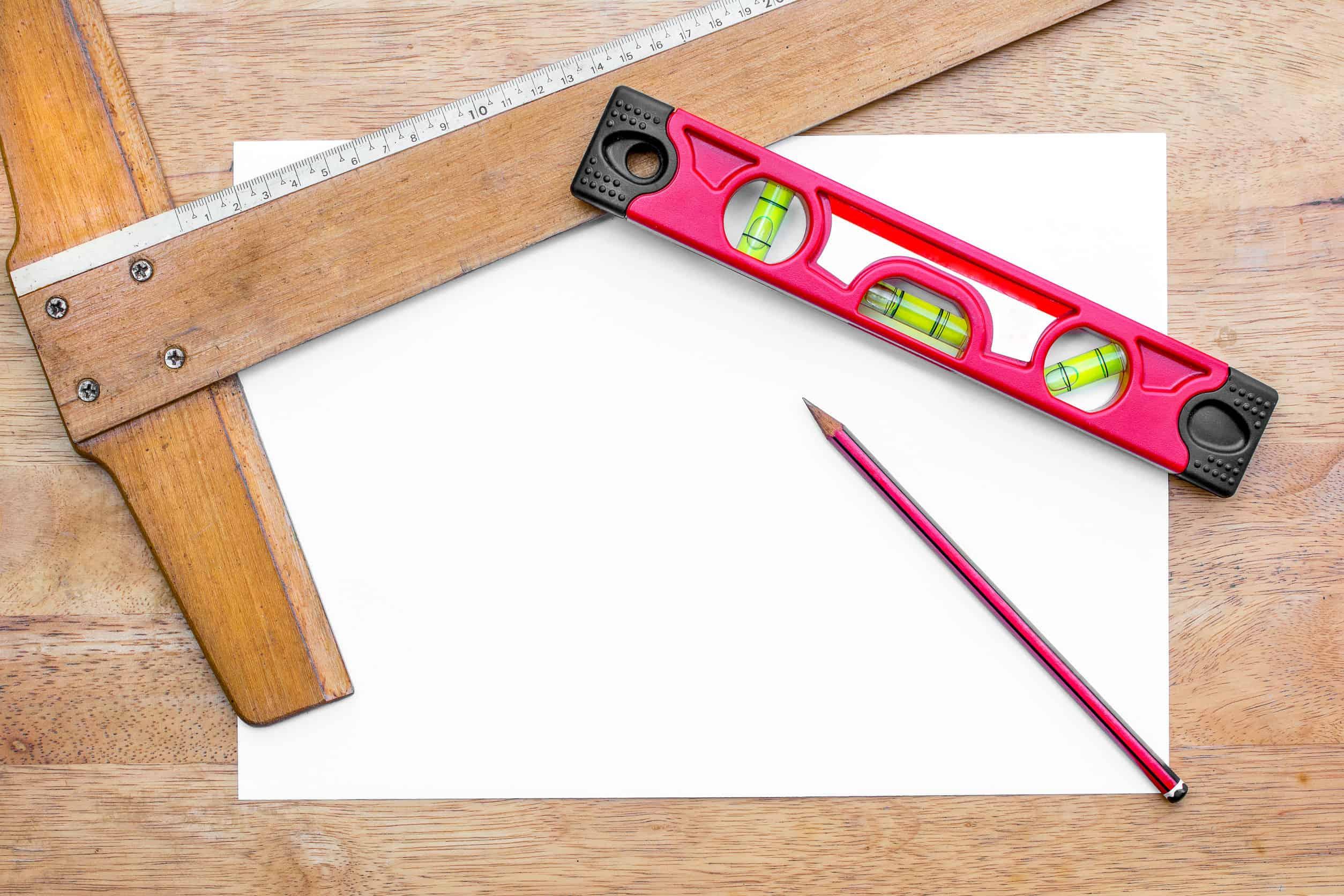Uma régua T, uma régua comum de plástico, um lápis e uma folha. Tudo está em cima de uma superfície de madeira.