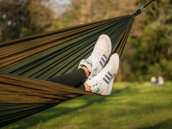 Na foto uma pessoa deitada em uma rede usando tênis Adidas brancos.