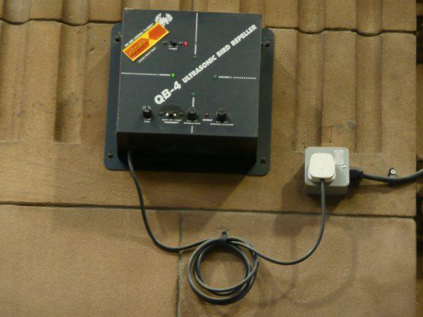 Imagem mostra um repelente eletrônico para pássaros conectado a uma tomada.