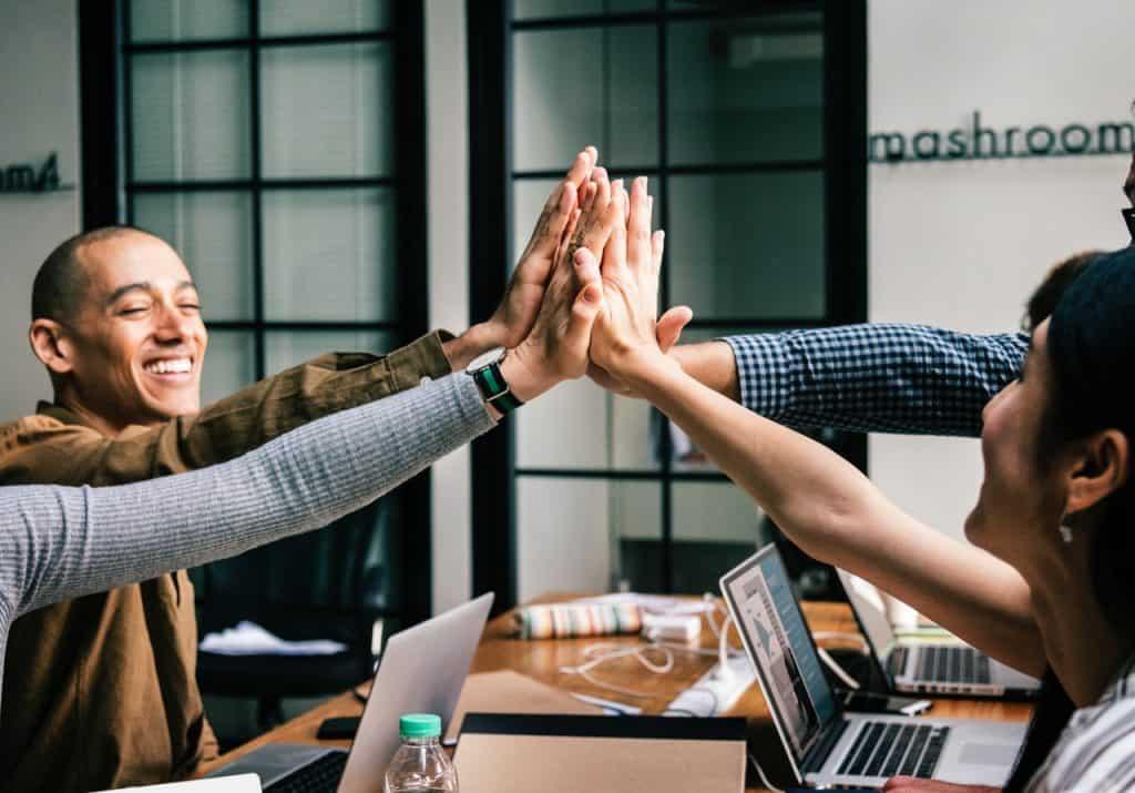 Na foto quatro pessoas em um escritório comemorando sentadas em uma mesa.