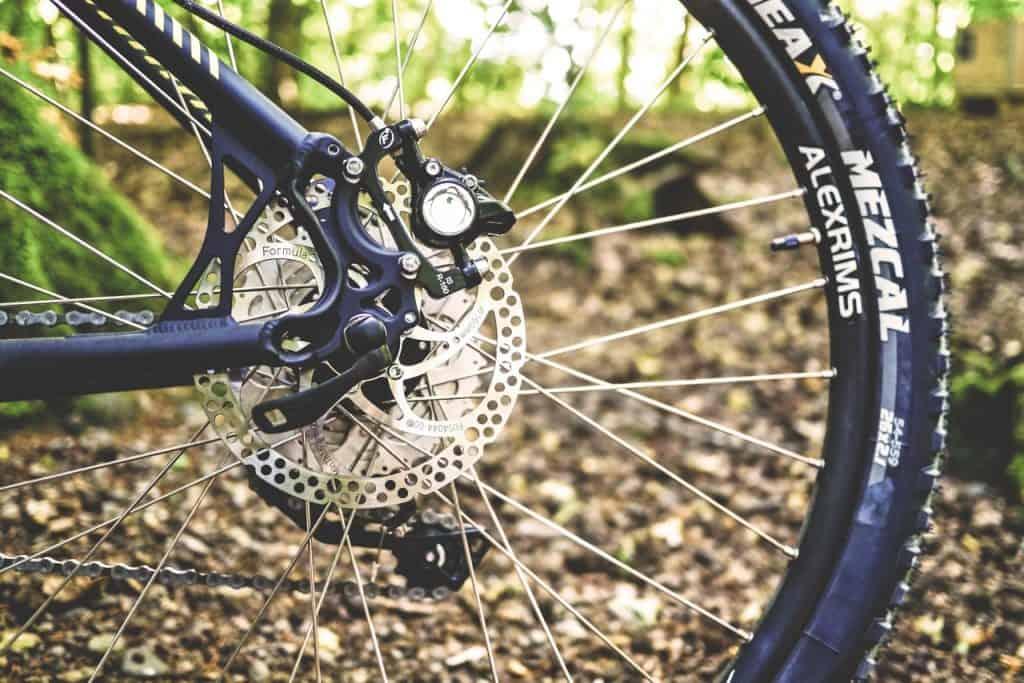 Imagem mostra o close da roda de uma mountain bike e seus aros.