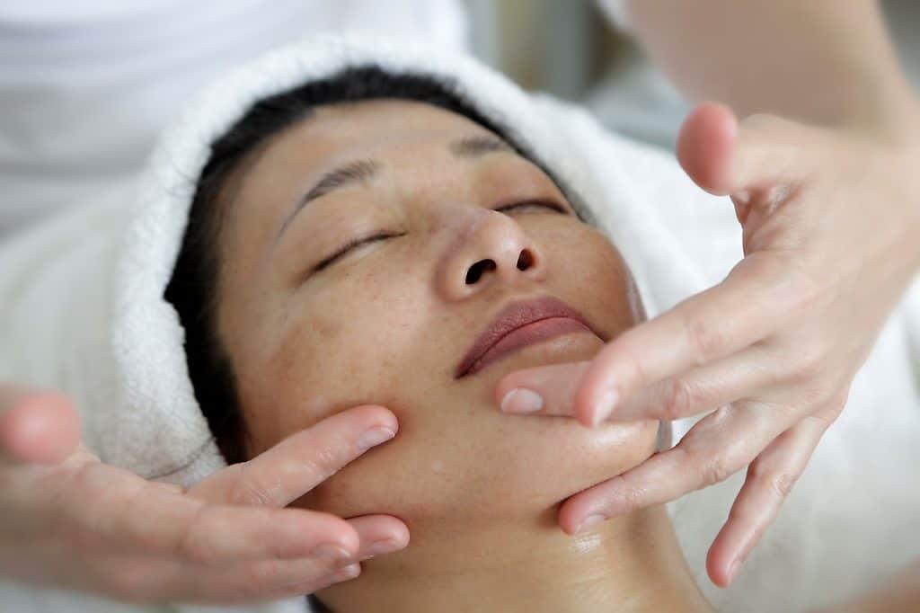 Na foto uma mulher deitada recebendo massagem no rosto.