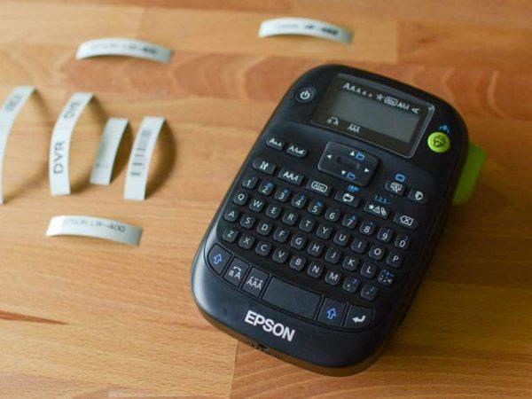 Imagem mostra um rotulador da marca Epson com algumas etiquetas impressas ao lado.