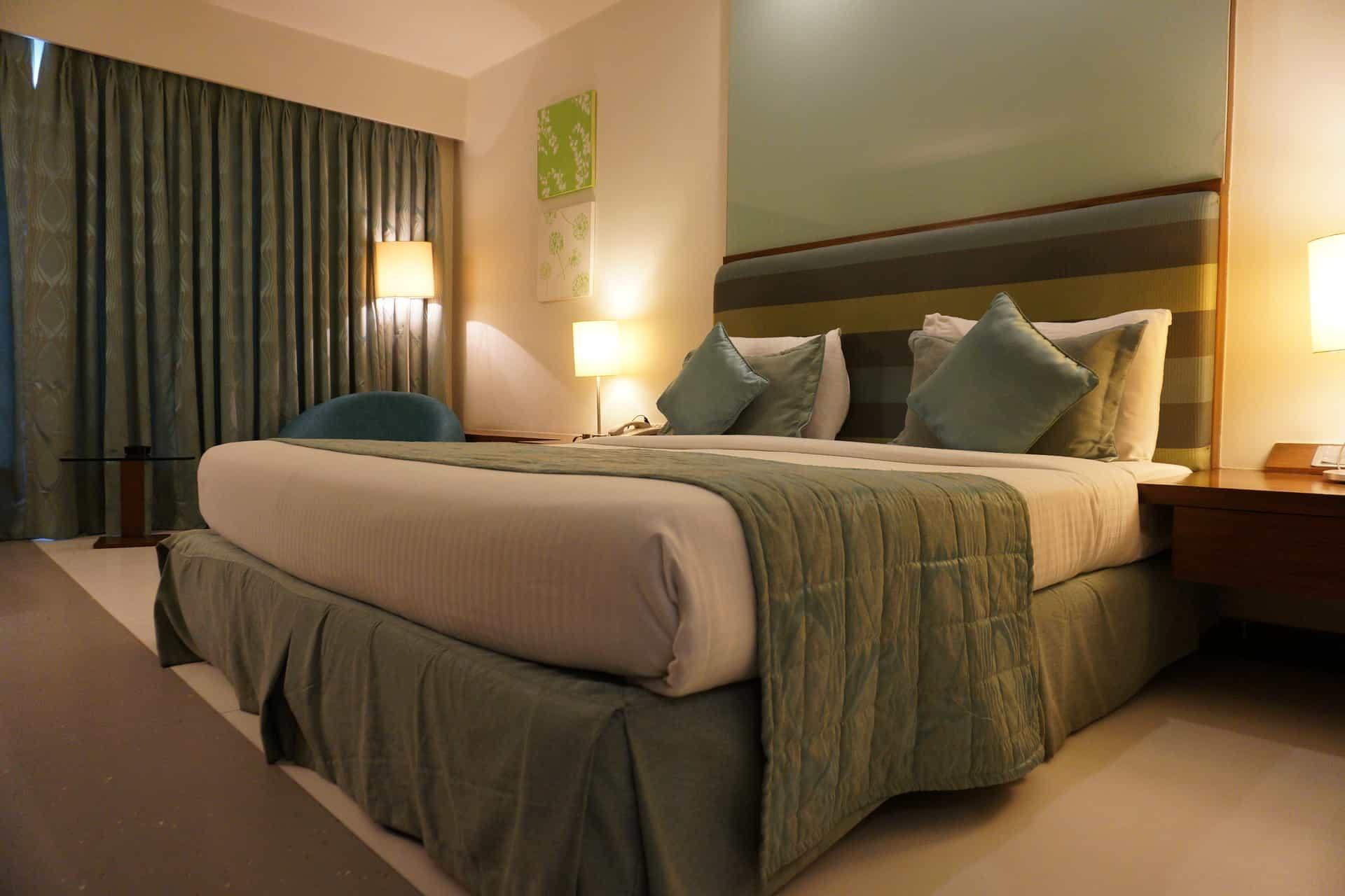 Imagem de quarto com cama box com saia em tons combinando com a cortina e a roupa de cama.