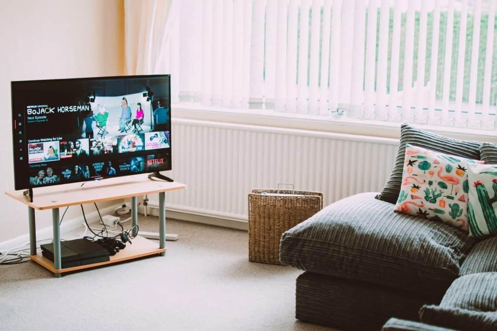 Na foto está uma parte de uma sala de estar com um sofá cinza com almofadas coloridas no canto direito e uma televisão em cima de uma mesa pequena de madeira.