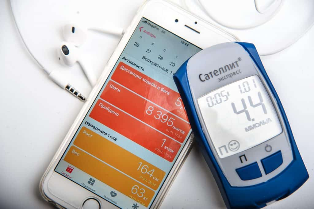Imagem de medidor de glicemia e celular.