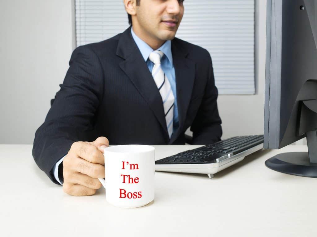 Homem sentado em sua mesa trabalhando bebendo café com caneca personalizada.