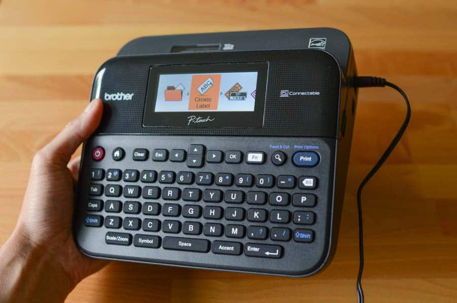 Imagem mostra uma pessoa segurando um rotulador da marca Brother com uma das mãos.