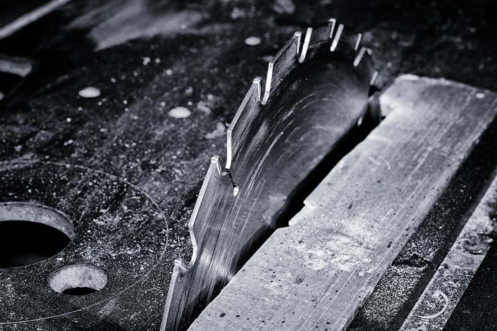 Um disco de serra serrando uma tábua de madeira. Foto em preto e branco.