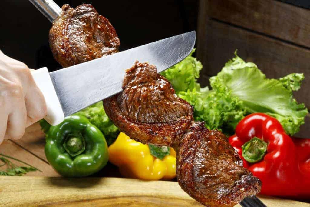 Mão segurando espeto com carne sobre tábua e fatiando com outra mão.