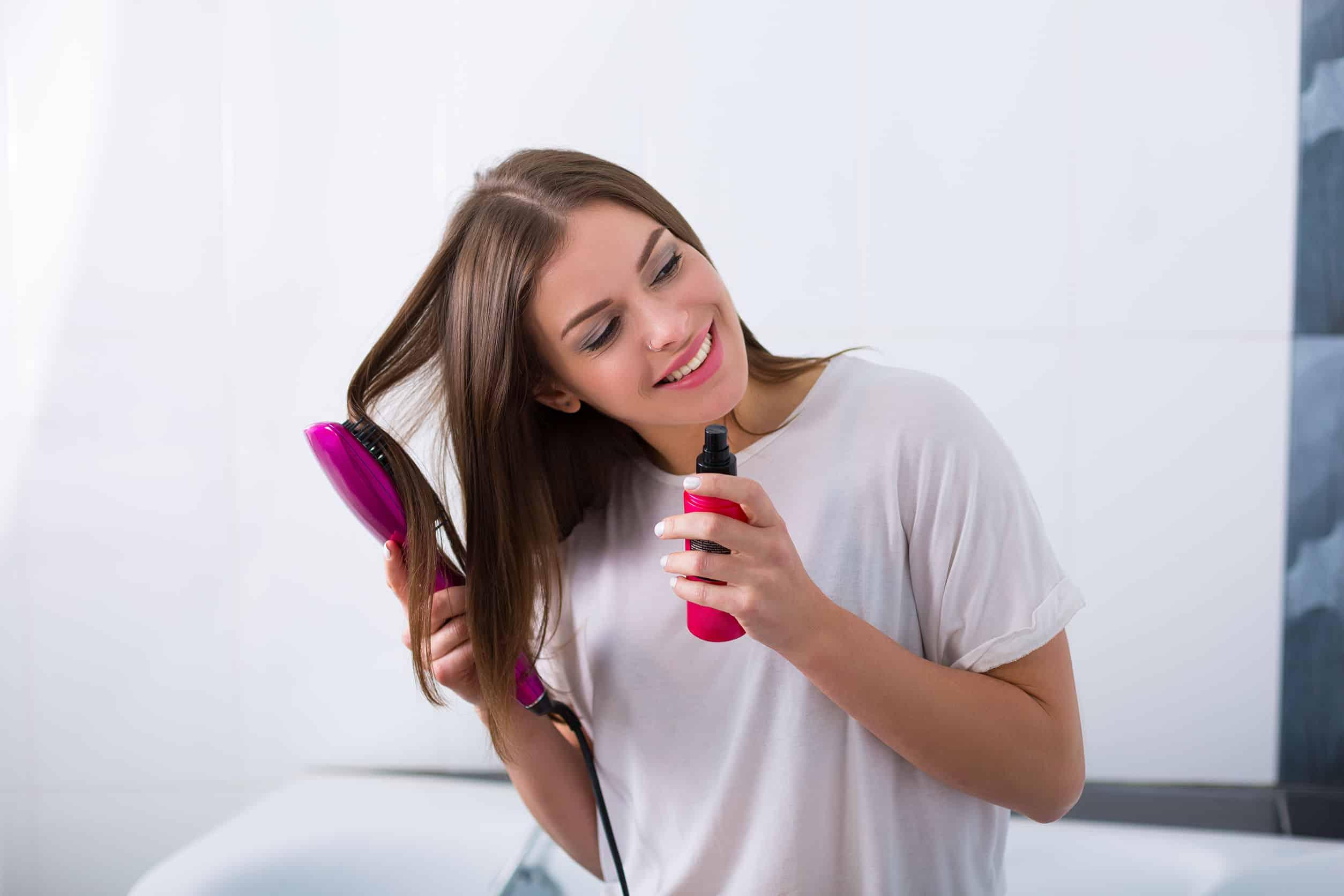 Foto de uma mulher passando escova e shampoo seco no cabelo.