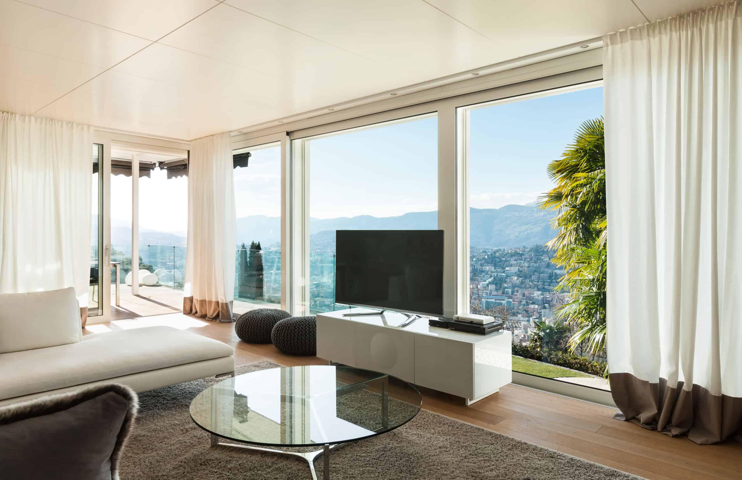 Na foto uma sala de estar com um televisor em frente a uma janela com a vista para a cidade.
