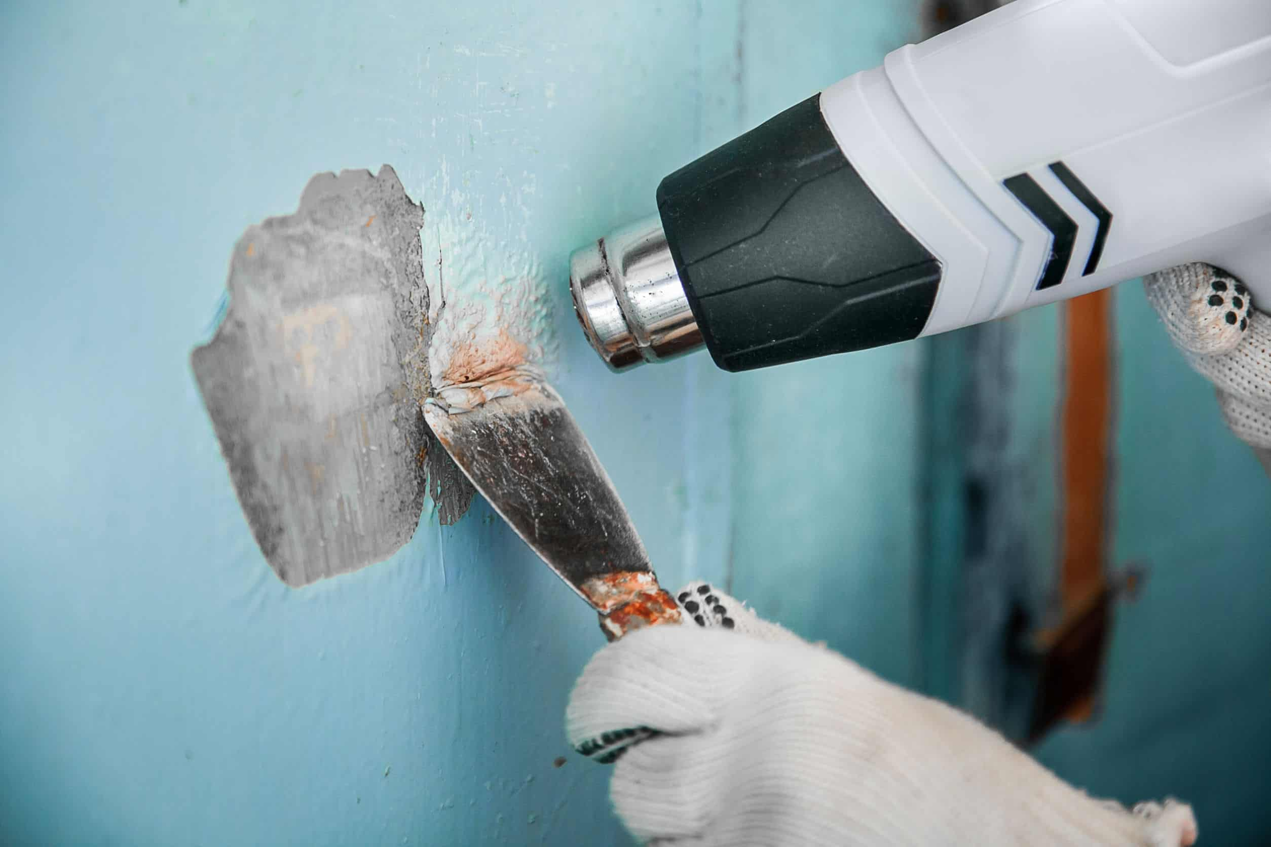 Imagem mostra um soprador térmico sendo usado para remover pintura de uma parede.