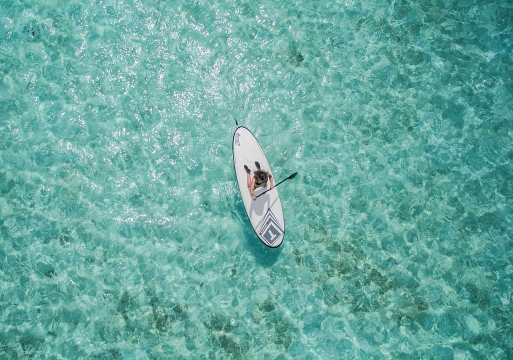 Imagem mostra, do alto, uma moça navegando ajoelhada em uma prancha de stand up paddle, em águas calmas e cristalinas.
