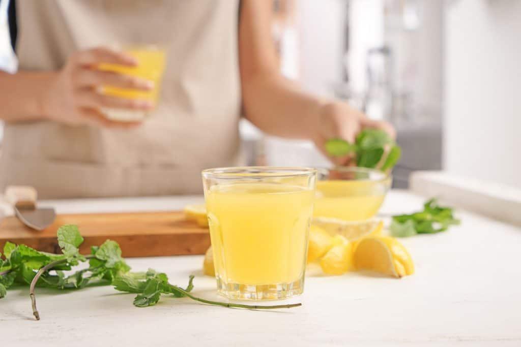 Suco de limão com alguns limões e folhas verdes ao lado e mulher ao fundo.