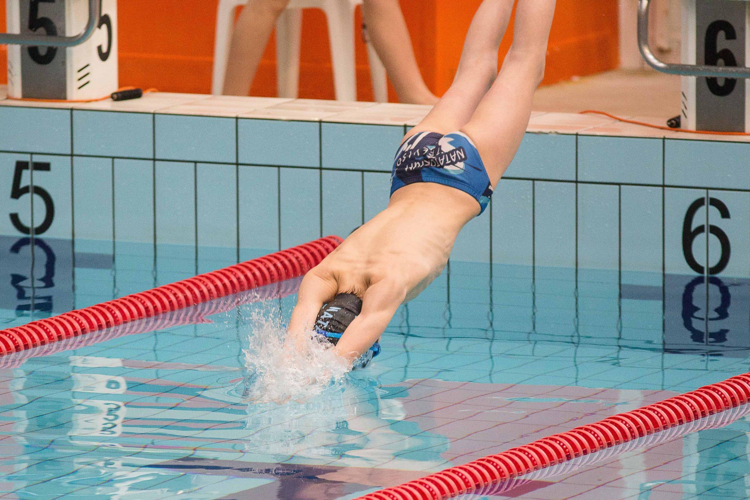 Imagem mostra um homem vestindo sunga mergulhando em uma piscina.