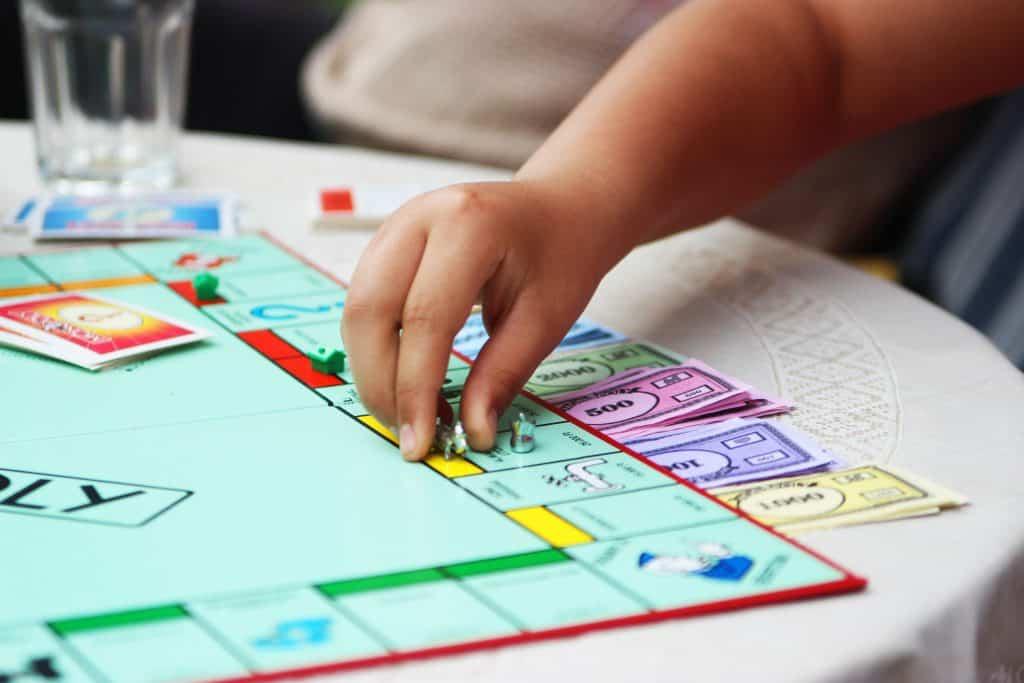 imagem de uma criança jogando Banco Imobiliário.