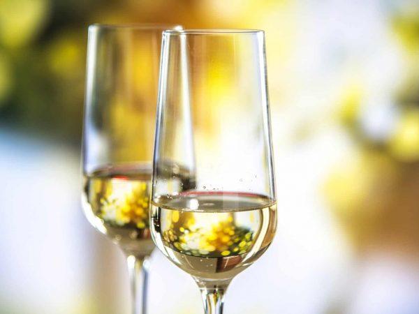 Foto de duas taças para champagne com um pouco da bebida dentro, em um fundo com blur.