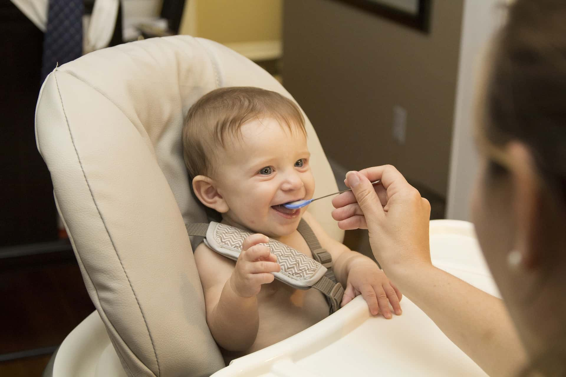 Imagem de criança sentada em cadeira de alimentação sendo alimentada por mulher com uma colher infantil.