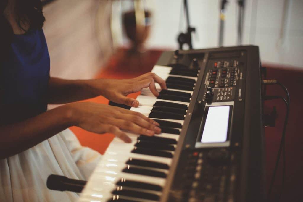 Imagem de uma mulher tocando teclado.