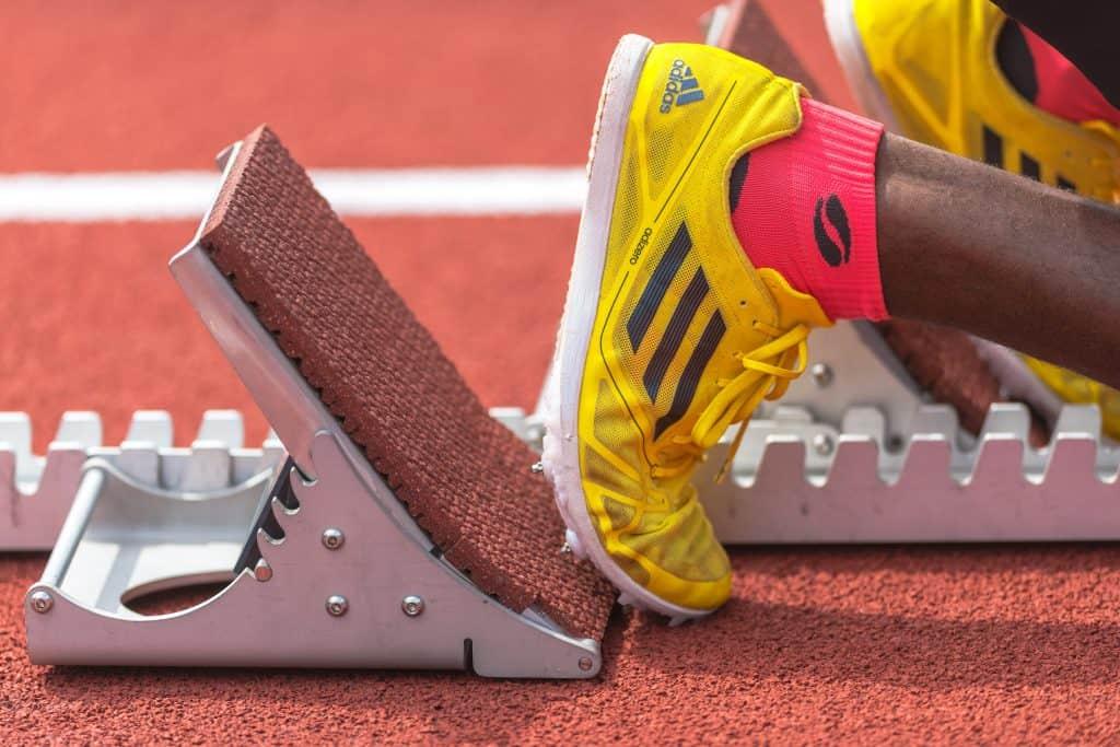 Na foto os pés de um corredor antes da largada de uma competição usando tênis Adidas amarelos.