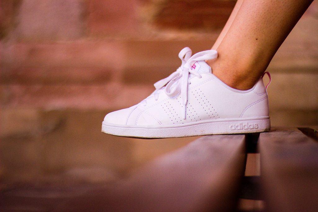 Na foto os pés de uma mulher usando tênis Adidas branco em cima de um banco de madeira.