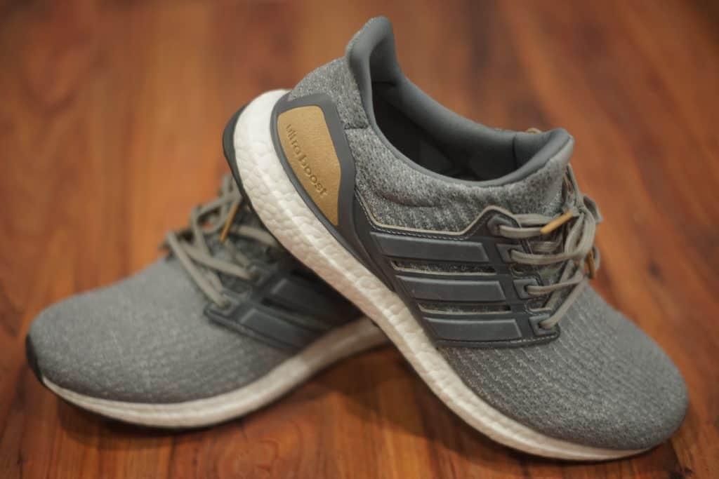 Na foto um par de tênis Adidas modelo Ultraboost cinza em cima de um piso de madeira.
