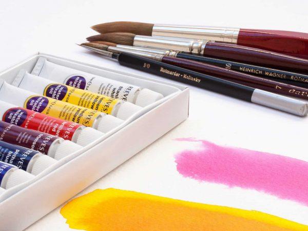 Kit de tintas óleo ao lado de pincéis sobre superfície usada para teste de cores.
