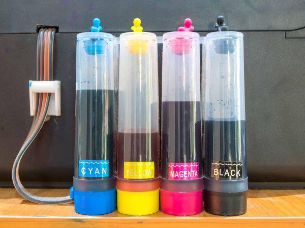 Bulk ink para quatro cores disposto ao lado de impressora.