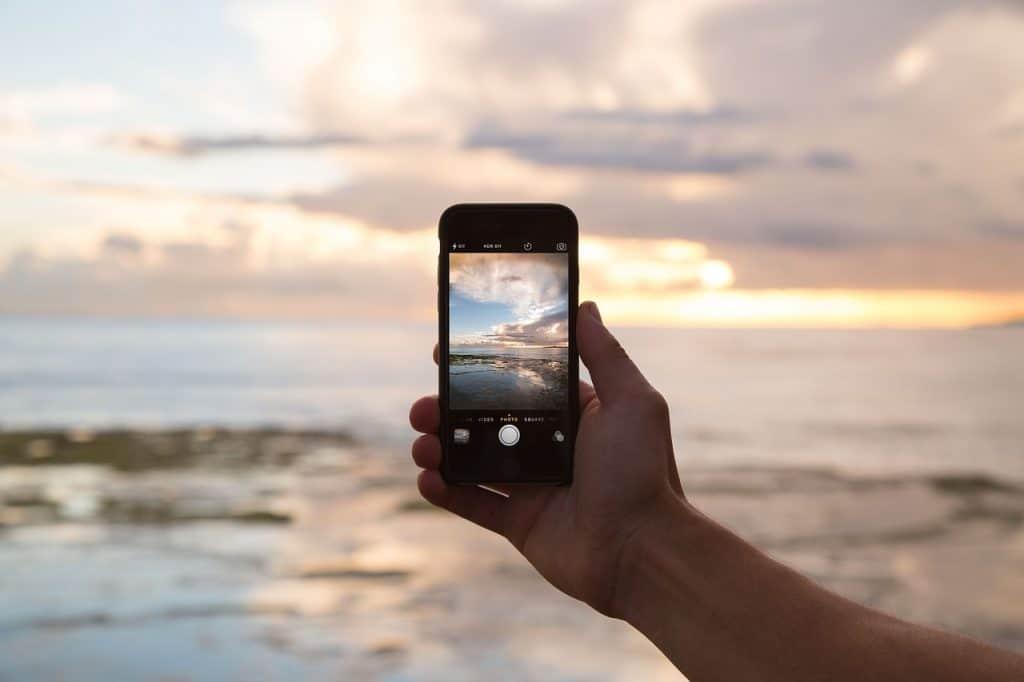 Na foto uma pessoa segurando um celular com a câmera para uma praia.