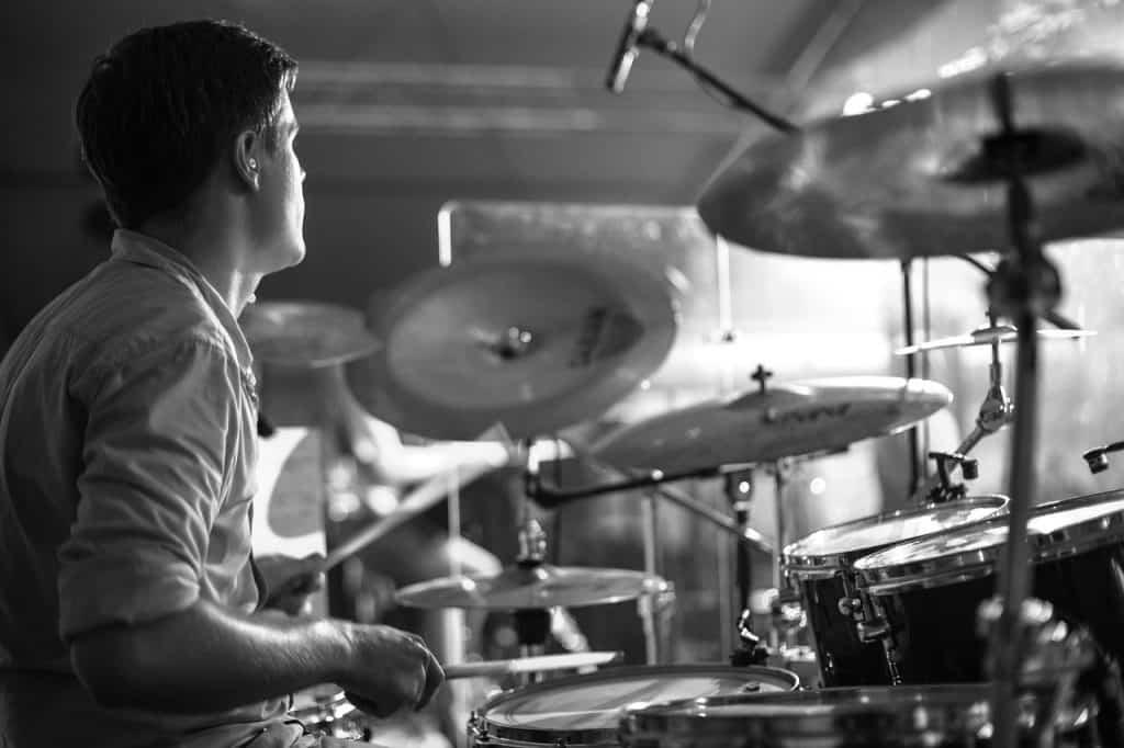 Imagem lateral de baterista performando em sua bateria acústica.