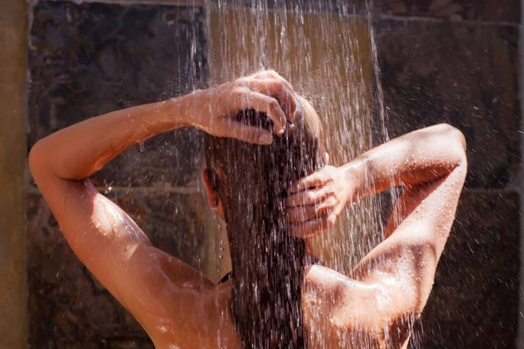 Mulher de costas tomando banho no chuveiro.