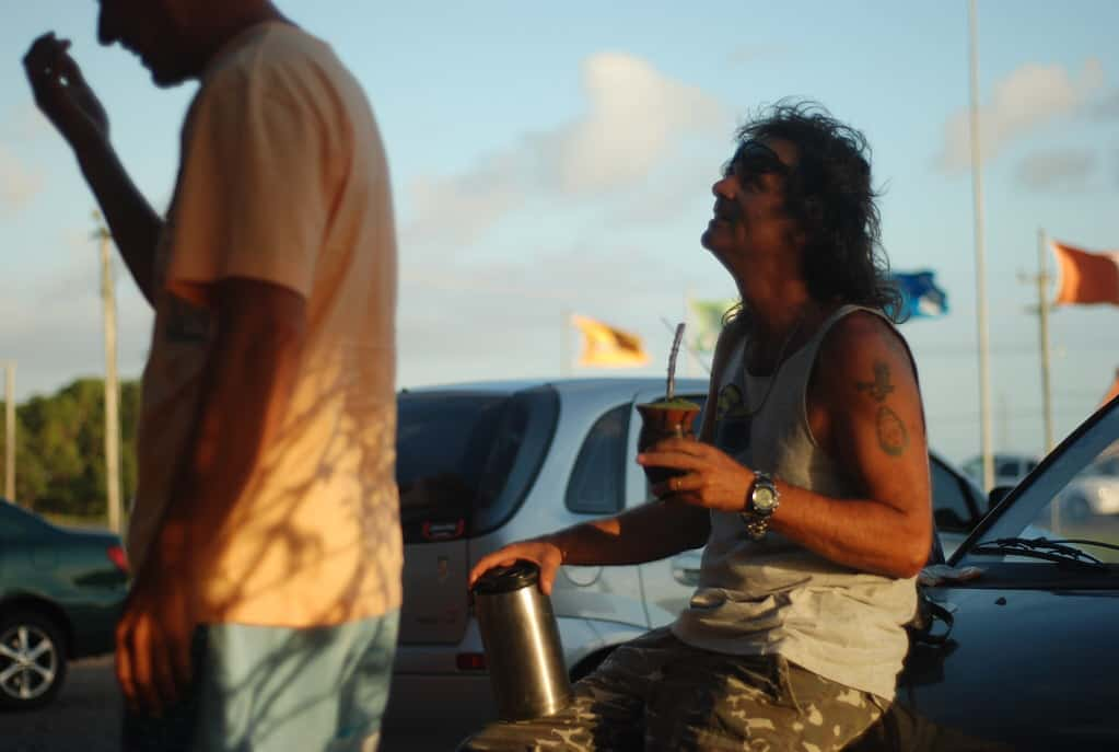 Homem tomando chimarrão, segurando cuia em uma mão e garrafa térmica na outra.