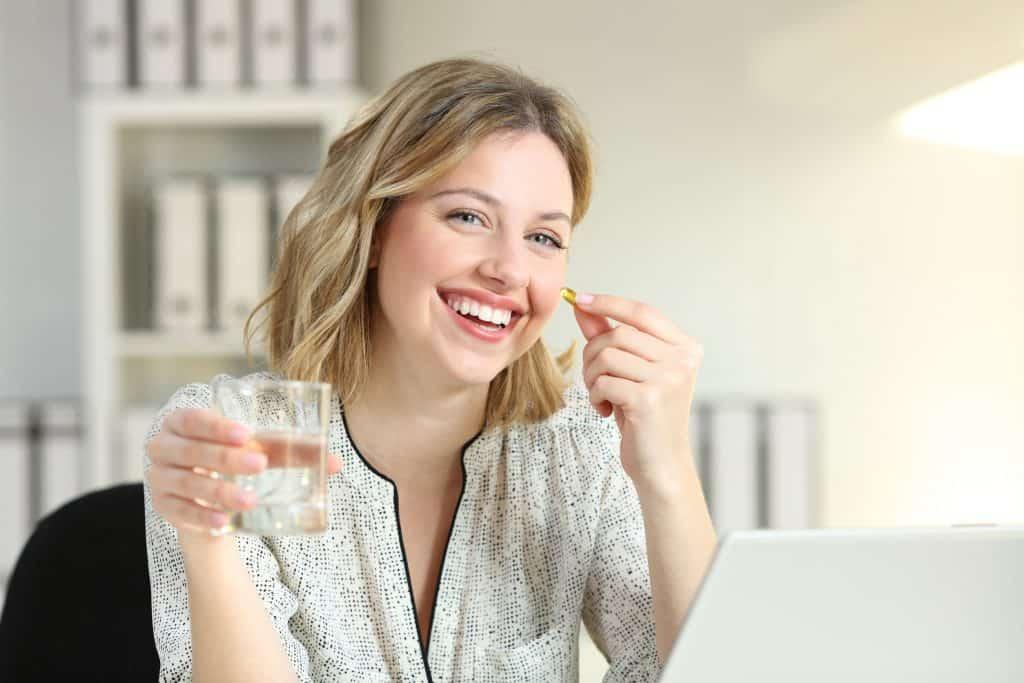 Imagem mostra uma mulher sorrindo ao levar uma cápsula de suplemento à boca. Na outra mão, um copo d'água.