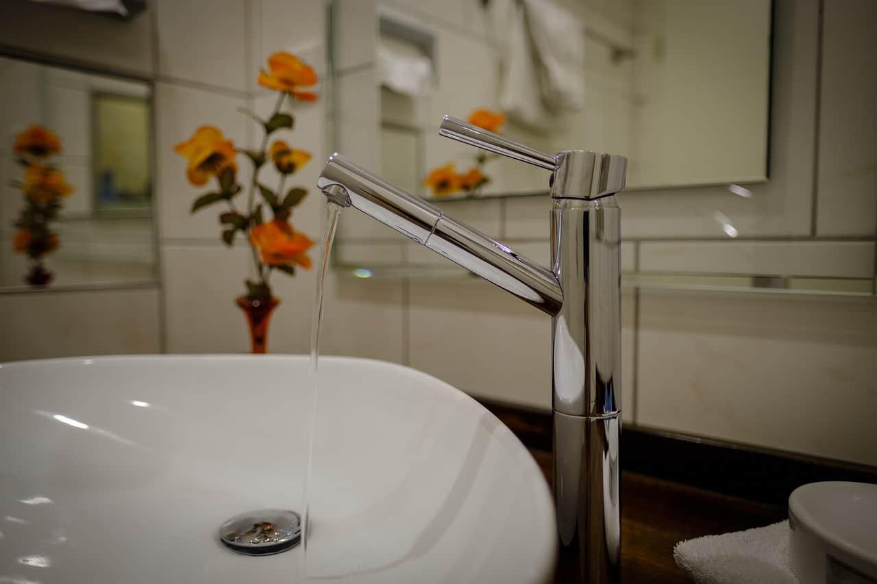 Na foto uma torneira prata de banheiro derrubando água sobre uma cuba branca com flores laranjas ao fundo.