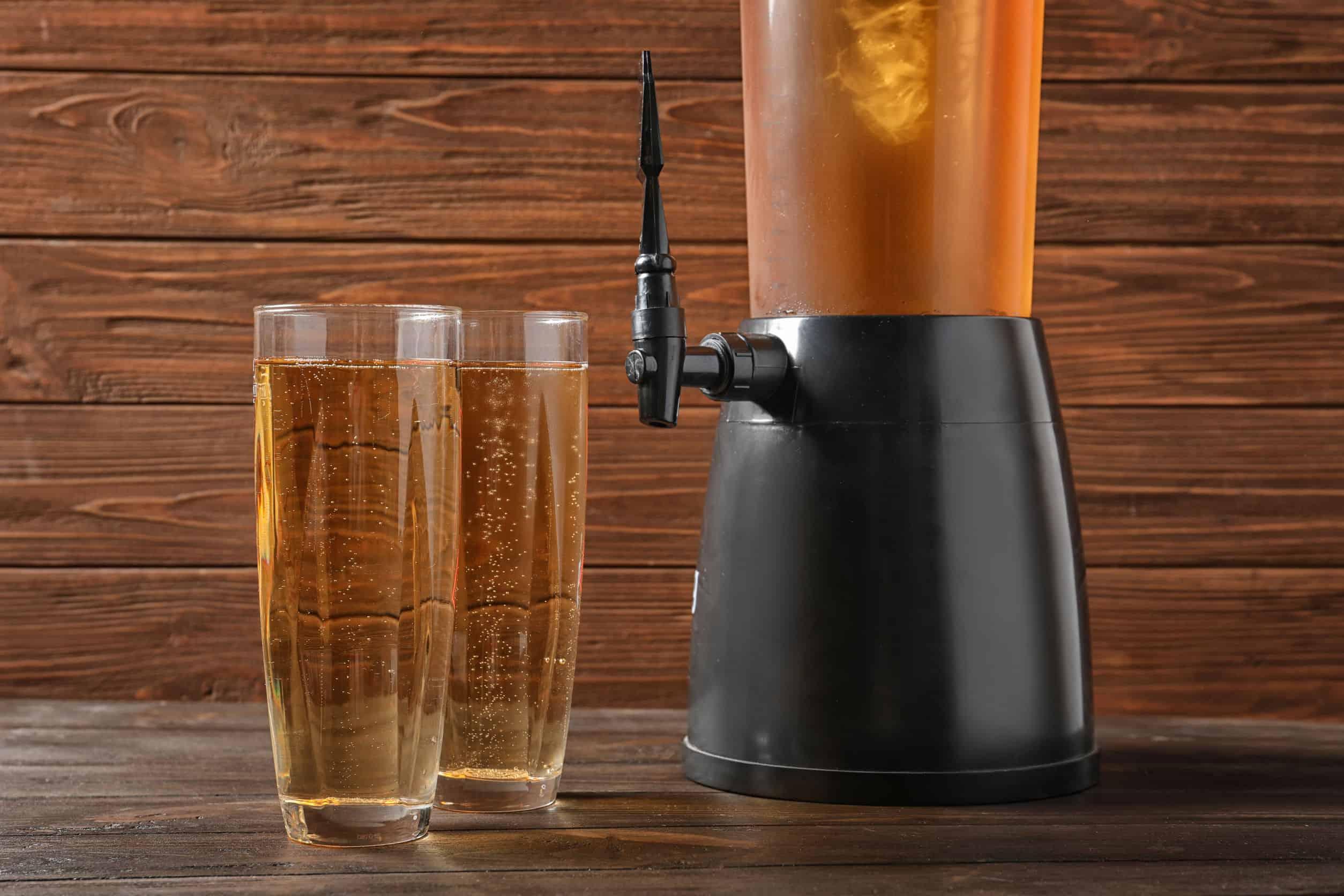 Imagem de torre de chopp e dois copos cheios.