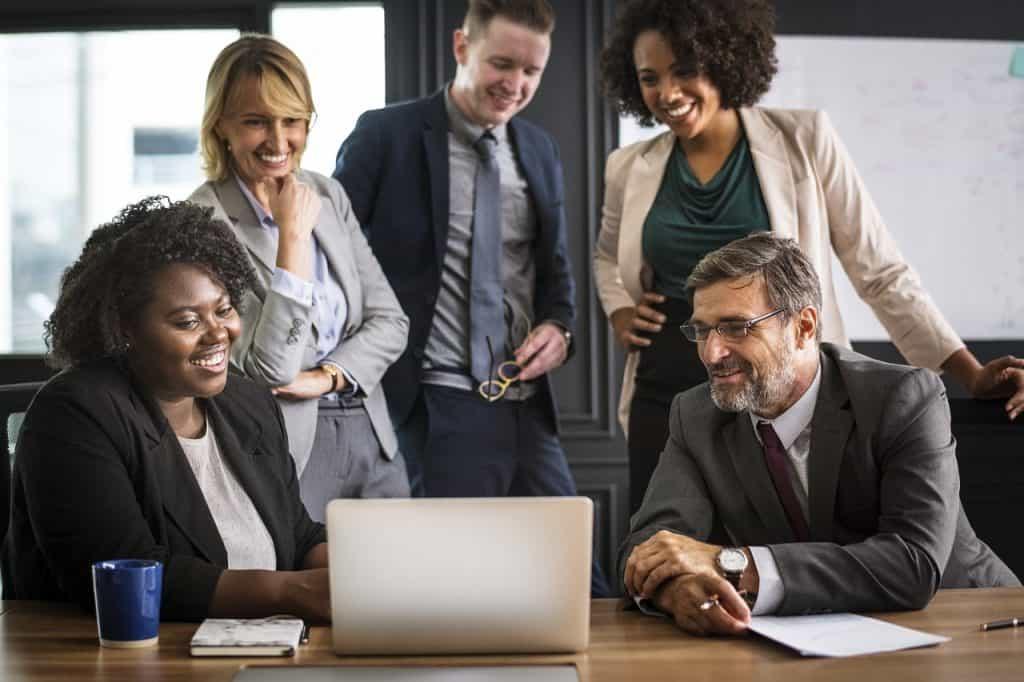 Imagem mostra cinco pessoas em volta de um notebook.