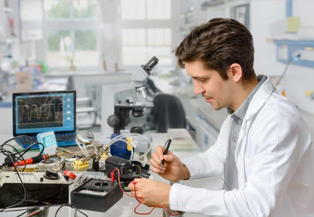 Profissional trabalha em osciloscópio digital ligado a computador.