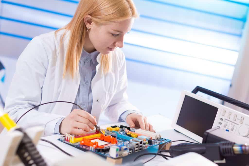 Mulher trabalha em osciloscópio digital.