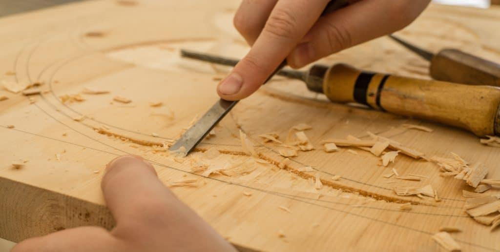 Imagem mostra entalhes sendo feitos manualmente em um pedaço de madeira.